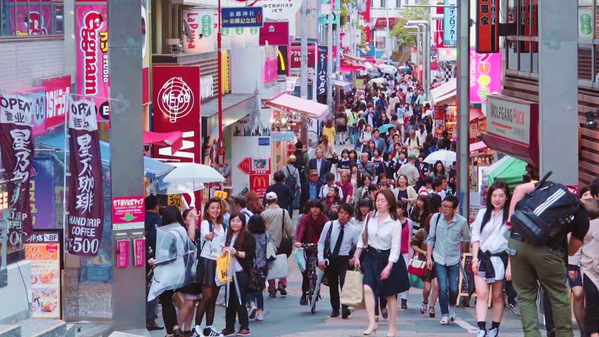 TOKYO - CIRCA JUNE 2015: People walk along Takeshita Street in Harajuku, Tokyo, Japan. Takeshita is a pedestrian-only street lined with cafes and boutiques famous for its fashion trends.
