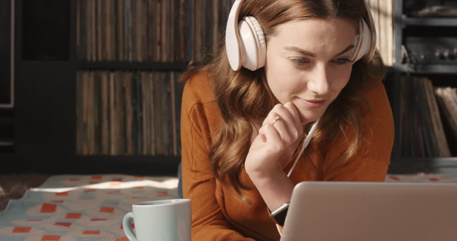 Beautiful woman listening to music on laptop at trendy home with headphones drinking coffee smiling vintage records in background orange retro colours and styling