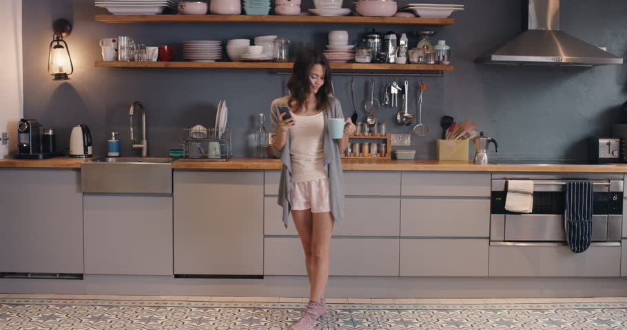 Happy young woman dancing in kitchen wearing pajamas in the morning listening to music on smartphone and coffee at home | Shutterstock Video #12273497