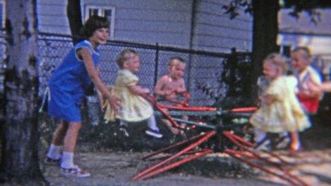 FLINT, MICHIGAN 1965: Ringleader troublemaker girl recklessly spinning small children on backyard playground toy.