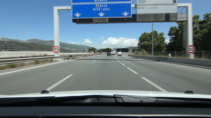 Driving north on highway A8 in Nice, France. Signs for Monaco and Nice.