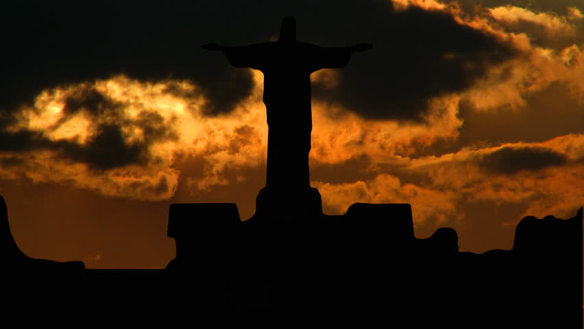 Statue of Christ on Sugar-loaf, in Rio de Janeiro, Brasil, with orange sunset in the background.