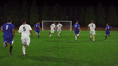 The camera follows a soccer player down the field as he makes a goal