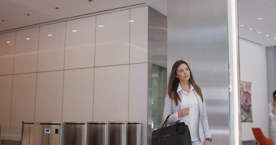 Attractive businesswoman using smartwatch leaving corporate office lobby after busy day at work happy expression real natural smile