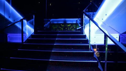 Walking by stairway in a nightclub.