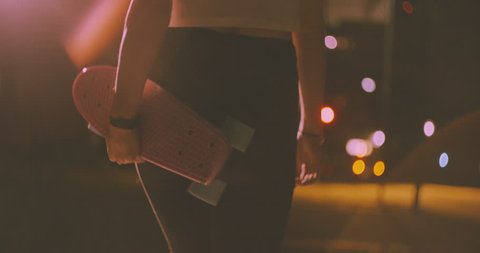 Rearview image of a skater girl walking at night alone with her pink skateboard on a city street