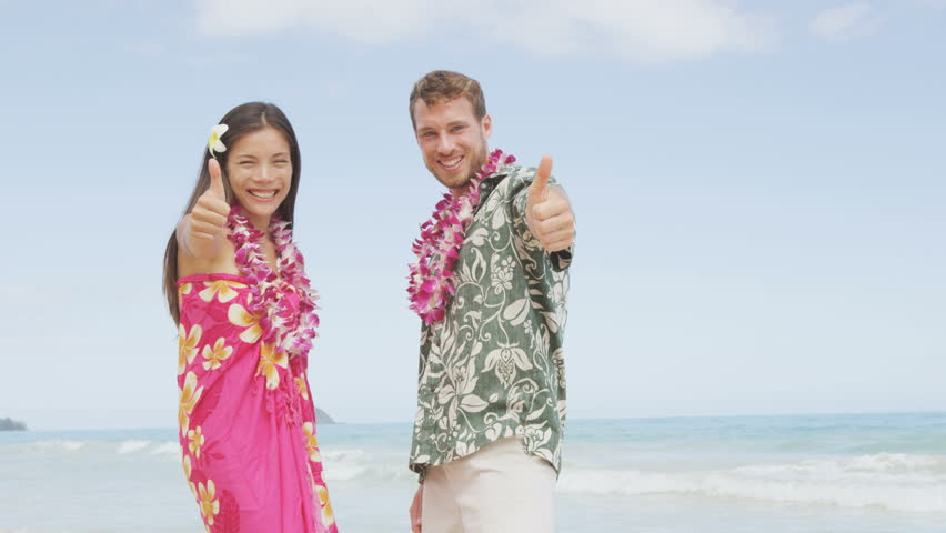 4a31e4133 Beach couple thumbs up happy excited on Hawaii in Hawaiian shirt. Portrait  of Asian woman and Caucasian man on beach standing with flower leis and  typical ...