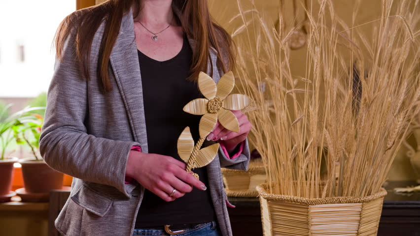 Lady hold a flower made from straws 4K. Beautiful knitted wheat straws crafted flower in young female person hands in front of big flowerpot with wheat.