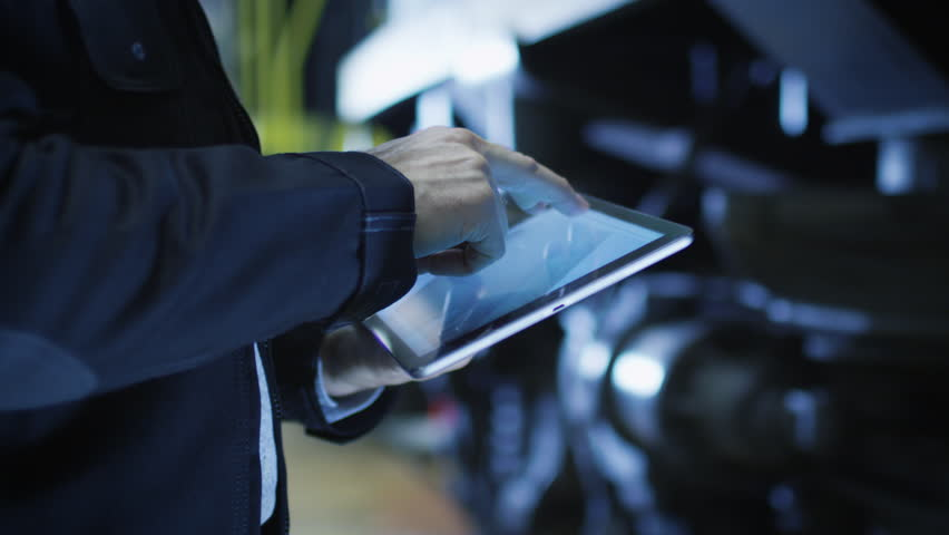 Technician in Hard Hat Using CAD Application on Tablet. Shot on RED Cinema Camera in 4K (UHD).