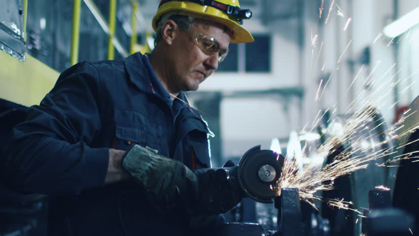 Worker with Angle Grinder does Metalworking in Industrial Environment. Shot on RED Cinema Camera in 4K (UHD).