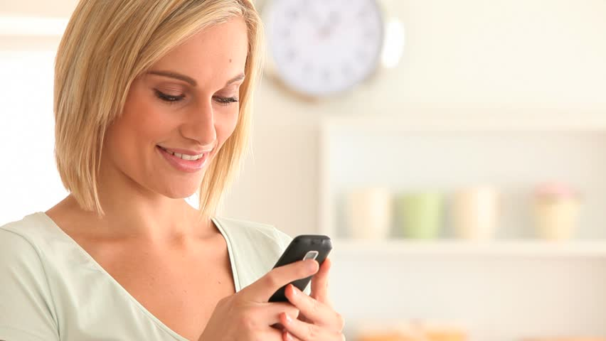 Smiling Young Woman Using Her Phone In Her Kitchen Stock Footage ...