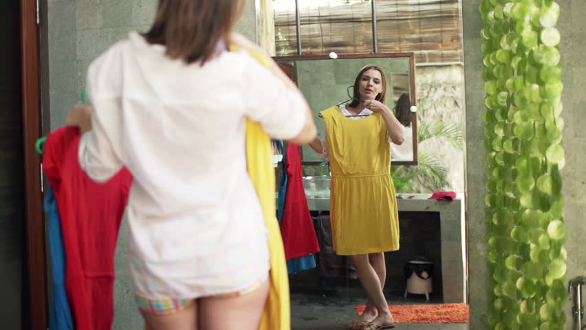 Young, pretty woman trying dresses in front of the mirror in bathroom
