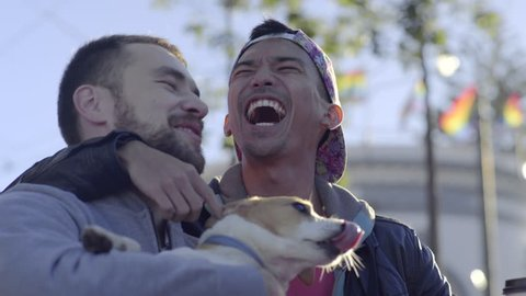 Cute Couple Hold Their Jack Russell Terrier And Get Dog Kisses, Men Kiss Each Other, Gay Pride Flags Blow In Breeze Behind Them