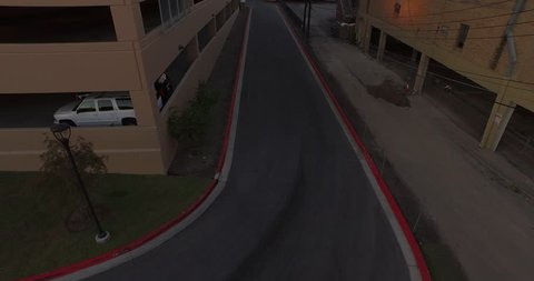 The camera flies down an alley and gains altitude revealing the Austin, TX skyline and Congress Ave bridge.