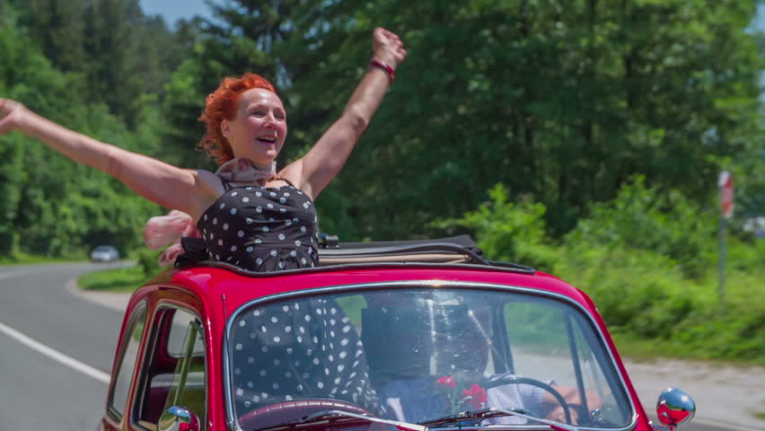 A senior lady is enjoying the ride in a small red vintage car. She circles with her arms and is smiling. There are a few cars driving behind the zastava car. The weather is sunny.