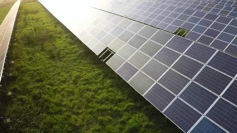 Aerial shot of solar farm at sunset moving backwards, medium shot.