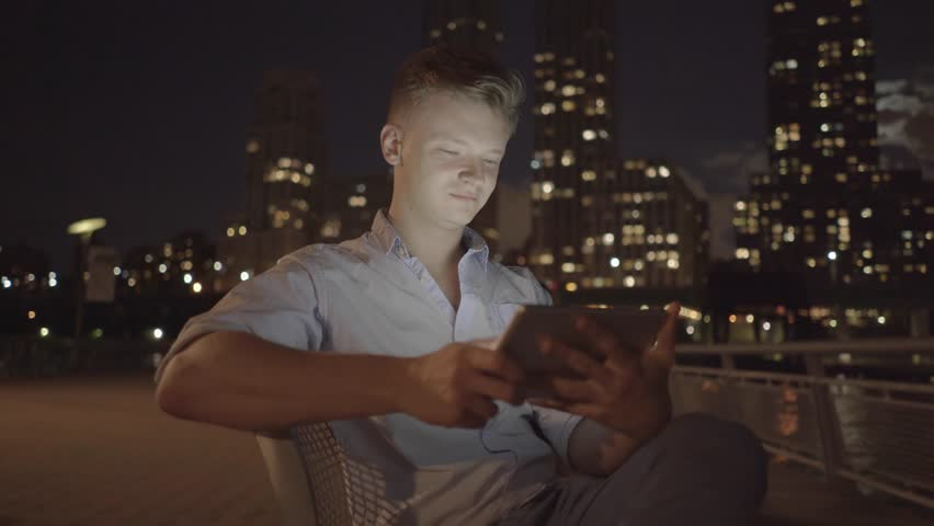 Young caucasian man using smart phone tablet outdoors searching the web. online social networking background | Shutterstock HD Video #12549014