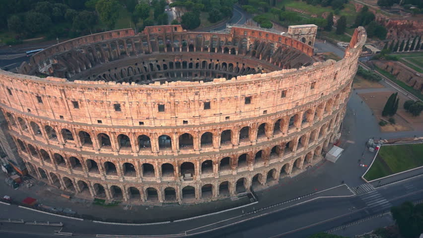 Colosseum, Rome, Italy. Aerial  Roman Coliseum on sunrise. Beautiful view of the famous Italian landmark travel icon in the Roman forum.