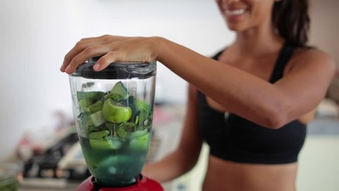 Young woman making a green juice on a blender