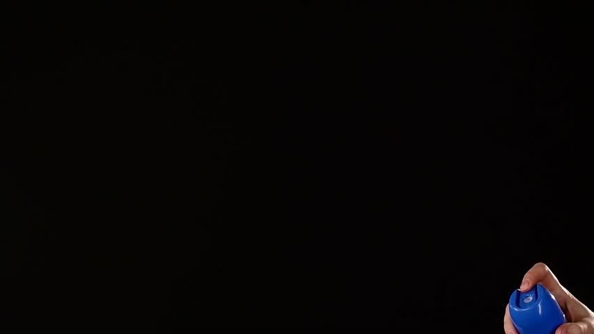 Air freshener on black background, slow motion