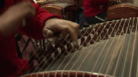 Beijing, China - February 2008: Close-up of hands, with fingerpicks on the fingers, plucking the guzheng Chinese zither in a music class. Beijing, China.