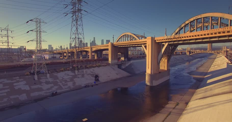 Historic Sixth Street Bridge over LA river in downtown of city of Los Angeles, camera ascending up aerial view. 4K UHD.