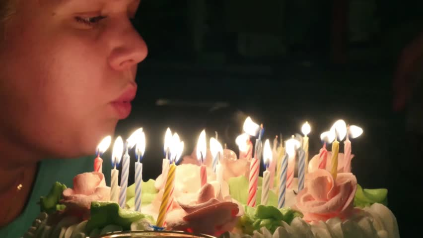 Blowing birthday cake candles