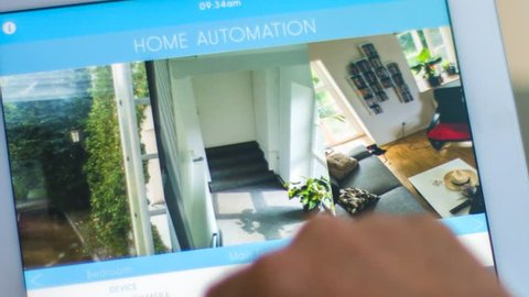 smart house, home automation, device with app icons. Man use tablet PC with smart home app to control his house ( surveillance camera ). the new generation of the internet of things.
