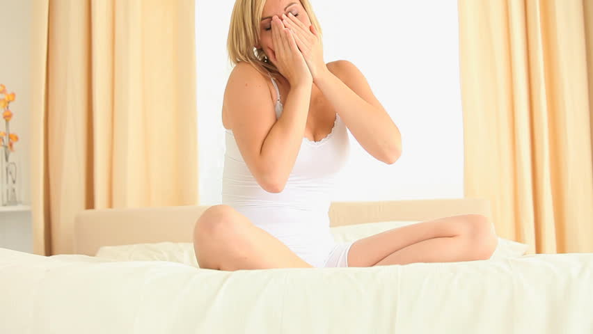 Young woman stretching her arms while waking up in her bedroom