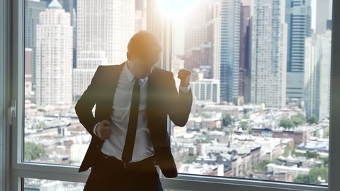 young successful business man dancing in modern office. cityscape skyline background