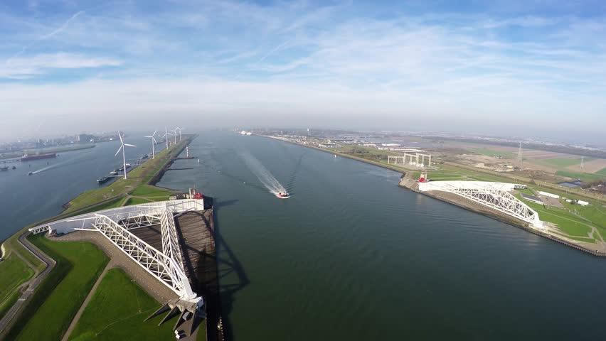 Aerial bird view of Maeslantkering a storm surge barrier on dividing line between Nieuwe Waterweg waterway located near Rotterdam one of largest harbors in world Delta Works Delta Werken Deltaworks 4k #12602474