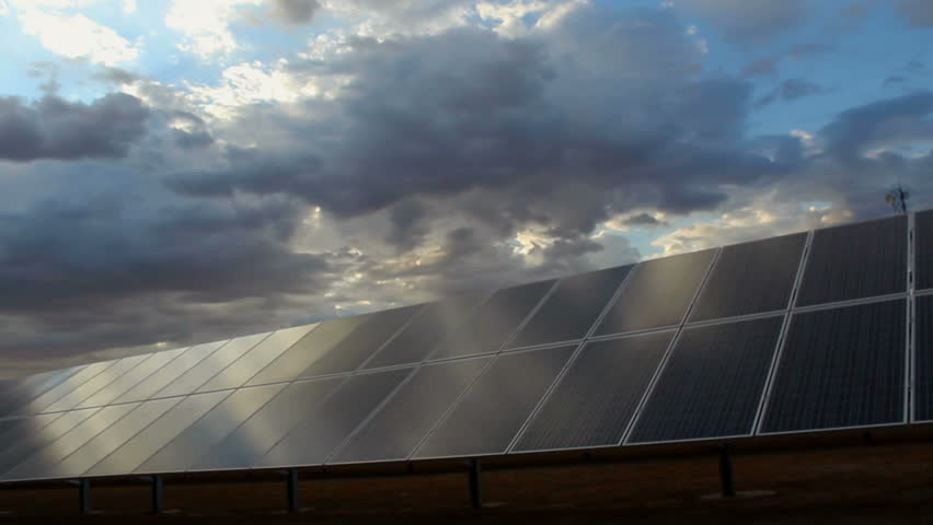 Time Lapse, Beaming, late afternoon sun rays sweep across solar panels creating beautiful green, energy scenic. 1080p