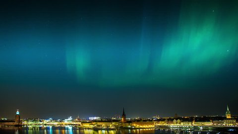 Northern Lights in full display over the bay Riddarfjärden in central Stockholm, Sweden showing the City Hall to the left.