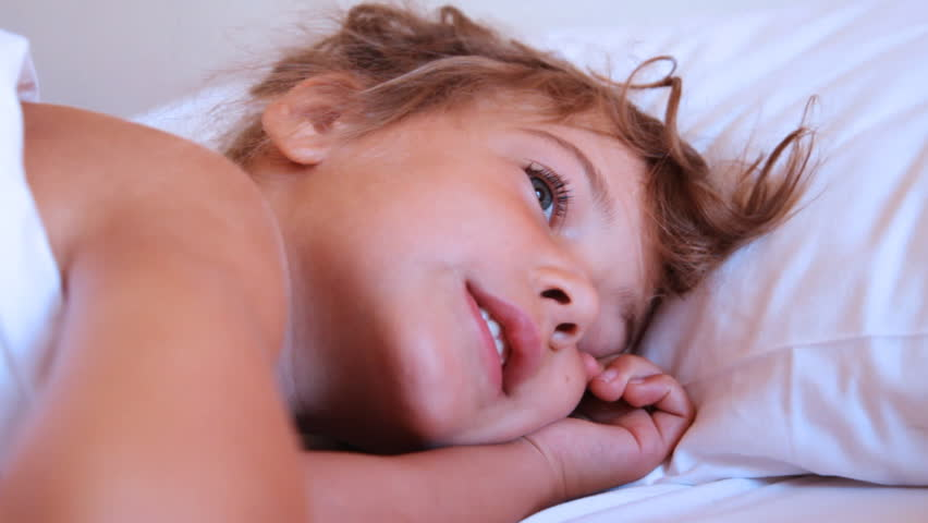 someone trying to wake up cute little smiling girl on pillow