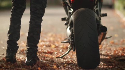 Man Gets on Motorcycle and Rides Away through City Streets with Autumn Leaves.  Male Motorsports Athlete Mounts Black Streetbike and Speeds Off Down Road