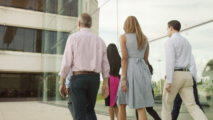 4K Attractive mixed ethnicity business team walking together outside modern glass office building. Shot on RED Epic.   Shutterstock HD Video #12630404