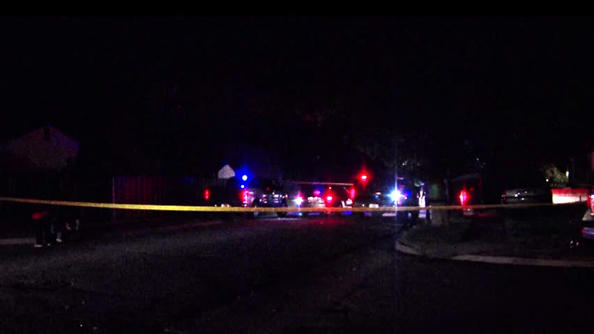 Police crime scene with emergency responders and tail lights flash in background at night.