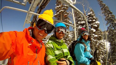 Friends on ski chairlift smile and laugh at camera.