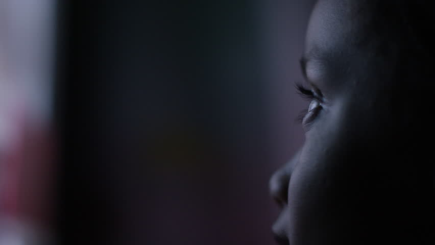 4K Profile of child's face watching a colourful screen in the dark