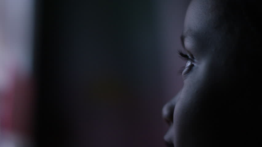 4K Profile of child's face watching a colourful screen in the dark, in slow motion