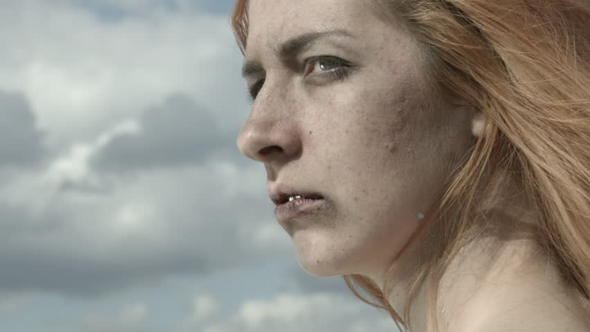 Scream. The girl's screaming against the sky with clouds. The blood splatter on the face.