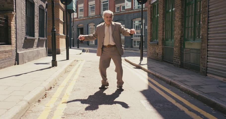 Happy elderly dancer man wearing suit funky street dancing freestyle in the city | Shutterstock HD Video #12658772