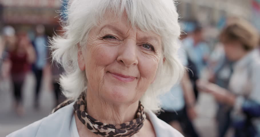 Slow Motion Portrait of happy mature old woman smiling in city real people series #12659333