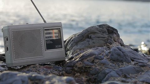 Listening a vintage FM/AM radio on the beach - close up, copy space