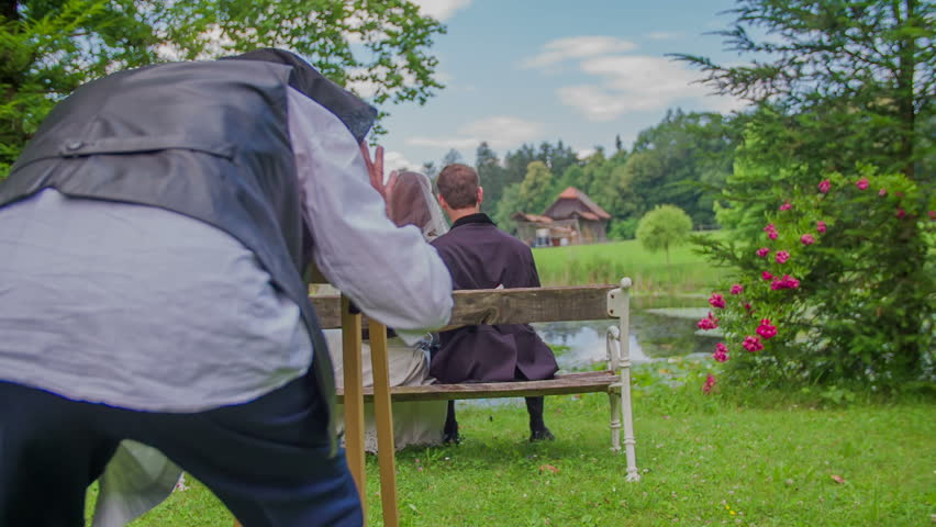 A photographer is taking a photo of the couple in the park. He is shooting a photo from behind. The couple is sitting on a bench | Shutterstock HD Video #12673694
