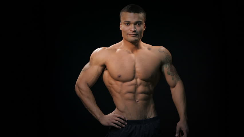 Muscular and fit young bodybuilder fitness male model posing over black  background. Muscular man bodybuilder. Man posing on a black background, ...