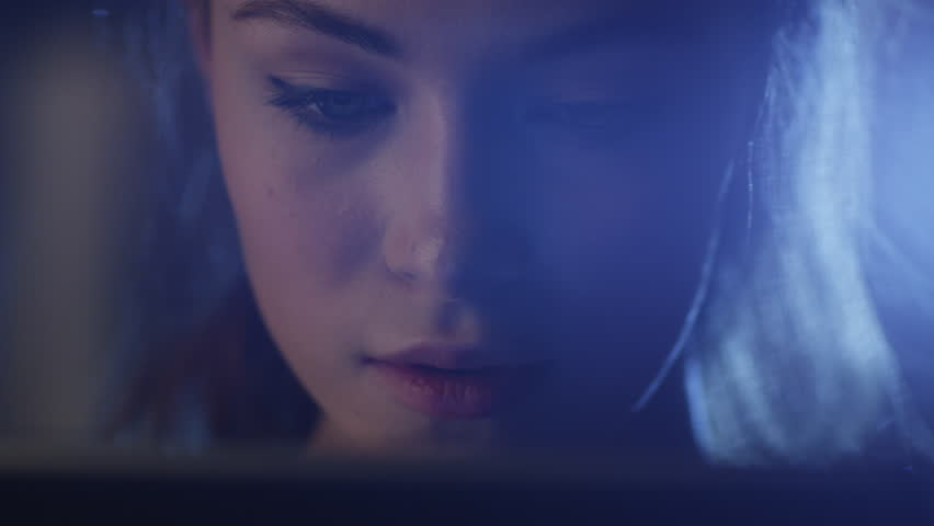 Portrait shot of a beautiful young girl looking a working tablet in the dark. Shot on RED Cinema Camera in 4K (UHD).