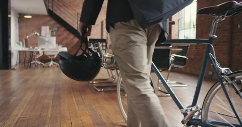 Young businessman arriving at work pushing bicycle through trendy office carrying helmet