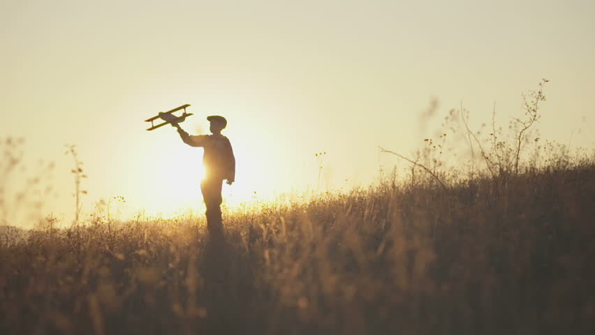 Happy kid playing with toy airplane against orange sun summer sky background. Boy playing airplane on a summer field. Best childhood concept. | Shutterstock HD Video #12743384