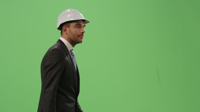 Businessman in a hard hat and a suit is walking on a mock-up green screen in the background. Shot on RED Cinema Camera in 4K (UHD). | Shutterstock HD Video #12753344